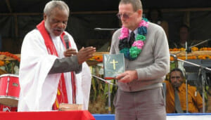The local pastor blesses the Ipili language New Testament held by LBT missionary Terry Borchard.